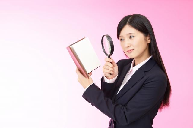 ノートと拡大鏡を持つビジネスウーマン